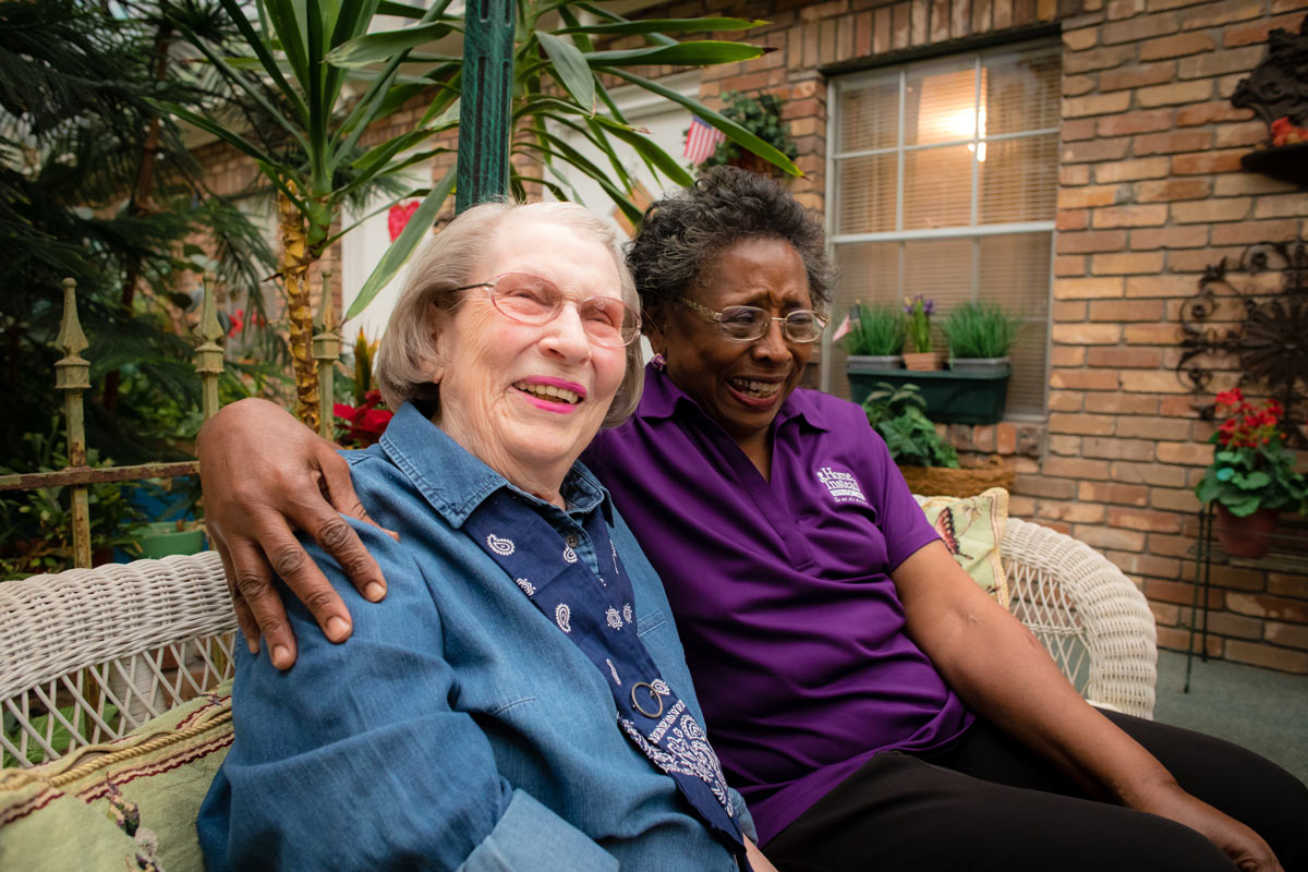Home Instead Caregiver cares for her senior client while sitting on outside patio.